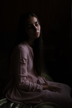 Girl sitting alone on bed in darkness