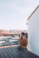 portrait of a bearded man on a rooftop talking by the phone
