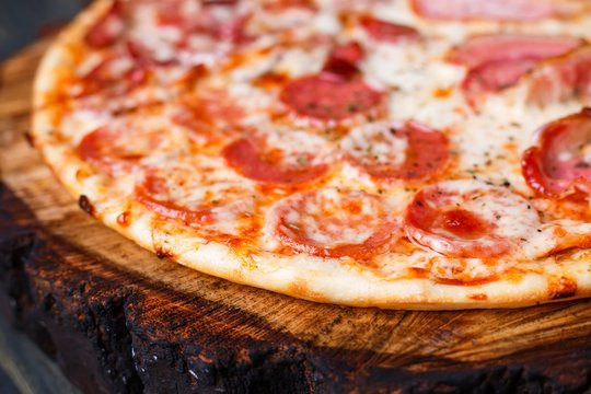 Appetizing fresh pizza with bacon, salami, ham and pepperoni, close up. Italian food, pizzeria concept