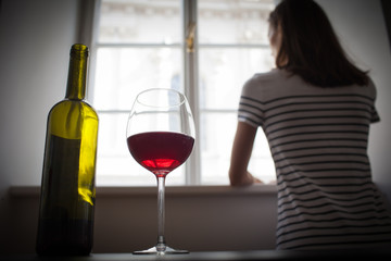 Woman looking out her window in a dark room drinking glass of wine. Sadness depression, alcoholism, loneliness concept.