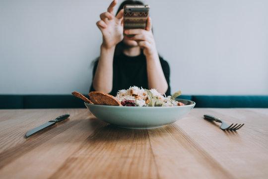 Woman taking food photo on smartphone camera