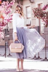 Outdoor fullbody portrait of young beautiful fashionable girl walking in street of european city. Model wearing stylish blouse, skirt, sunglasses, holding pink handbag. Spring, summer  fashion