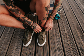 tattoed woman tying the laces of the sneakers