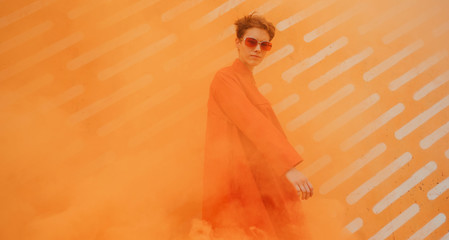Young woman with orange clothes surrounded by orange smoke