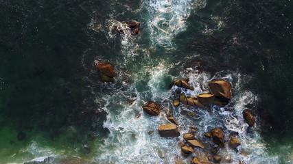 Sea water crashing on rocks - drone shot