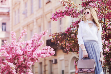 Wall Mural - Outdoor portrait of young beautiful girl posing in street of european city, blooming trees on background. Model wearing stylish sunglasses, holding pink bag. Female fashion concept. Copy, empty space