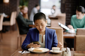 Smartphone addicted businesswoman at lunch