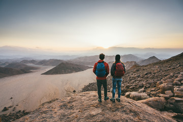 Hiking couple on a mountain summit watching the sunset over a desert wilderness
