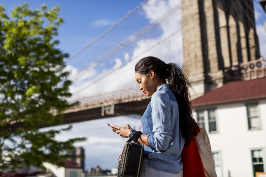 Woman using mobile phone outdoor.Brooklyn, New York.