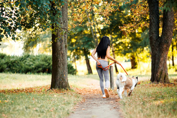 Sports woman walking with dog in the park.