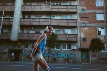 Urban Girl with headphones and longboard