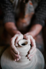 Talented  artisan working in pottery shop, making beautiful clay