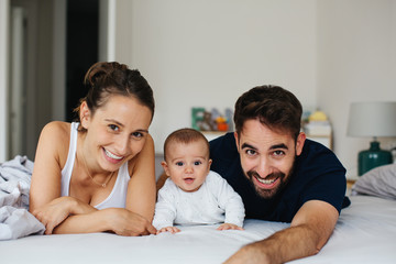 Happy family having fun with his baby boy at home.