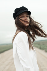 Beautiful young woman in a hat on a windy day