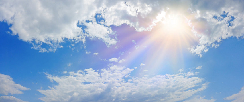 Miraculous Heavenly Light Panorama Banner -  Wide blue sky, fluffy clouds and a beautiful warm orange yellow sun beaming down radiating depicting a holy entity