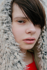 portrait of young fashion girl in fur coat in the wind