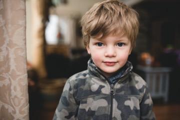 Little boy in jacket smiling in warm cabin
