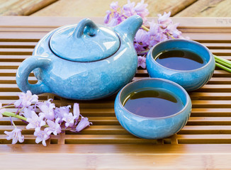 Blue ice crackle glazed ceramic tea pot with two cups of tea on a tray decorated with flowers