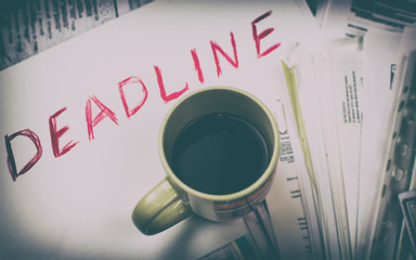 Deadline written on paper and a cup of coffee on scattered papers.