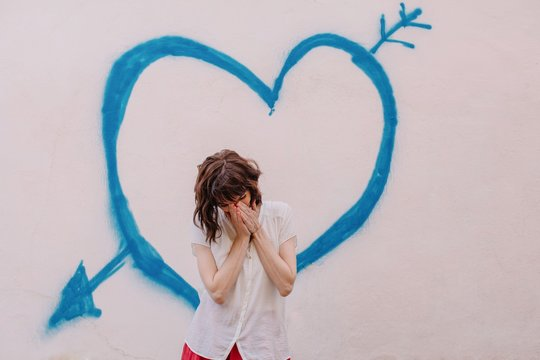Front view shot of lovely shy woman standing against the wall with painted heart with arrow