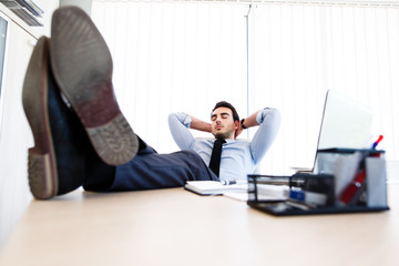 Young lazy businessman sleeps at office
