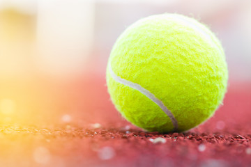 Sport Item concept : Tennis balls at red court in summer day. Tennis is racket sport that can be played individually against single opponent (singles) or between two teams of two players each.