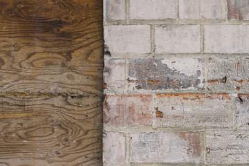 Close up worn brick and plywood wall