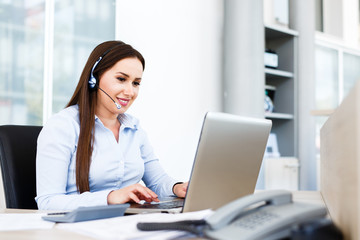 Beautiful young woman working on laptop with headphones