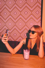 young woman sitting in the night club and taking selfie.