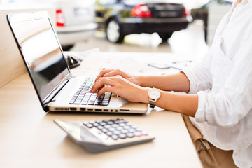 Car shop manager working on financial documents