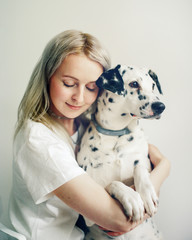 Woman embracing with Dalmatian dog