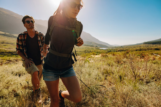 Young couple hiking together through extreme terrain