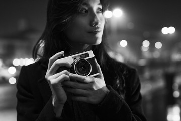 Female Asian photographer in the city at night