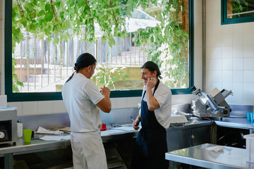 Two cooks talking in a relax moment in the kitchen
