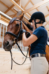 Young woman rider tacking up her horse in a barn