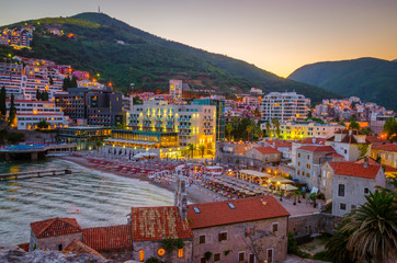 Aerial view on illuminated coastline and old town at night in Budva, Montenegro