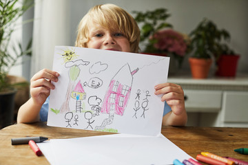 Child holding a drawing of a house and family