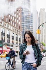 Woman using mobile phone while walking on New York streets