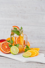 Citrus fruit and herbs water for detox or dieting in glass bottles. Limes and oranges