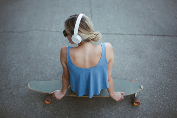 Girl with headphones and longboard