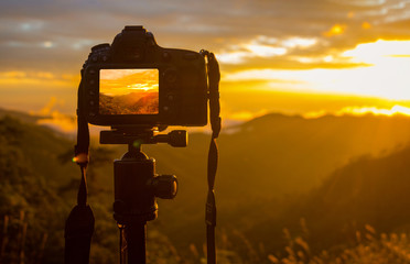 A DSLR camera  on tripod. It is on mountain. Photography on sunset and mountain