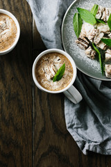 Mug of hot chocolate with marshmallow and mint leaf