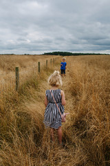 Two children walk beside a field full of long grass ready to be harvested for hay.