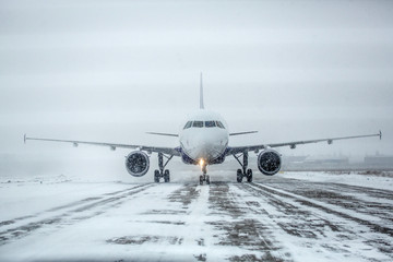 Türaufkleber Flugzeug Airliner on runway in blizzard. Aircraft during taxiing at heavy snow. Passenger plane in snow at airport. Modern twin-engine passenger airplane taxiing for take off at airport during snow blizzard