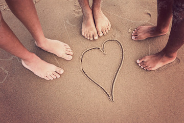 Racially diverse children's feet at the beach with a heart drawn in the sand