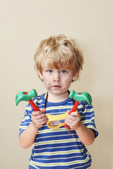 Silly young boy holding toy hammers with scribbling on his face