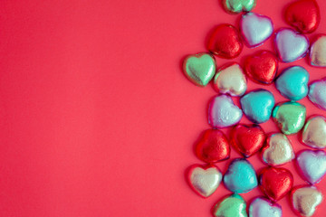 Red background with multicolored heart rests in the concept of Valentine's Day.