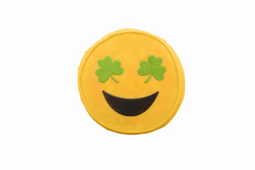 yellow smiley cookie with shamrocks instead of eyes. the concept of St. Patrick's Day. Yellow emoji cookie.  Isolated on a white background.  top view, flat lay