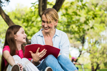 Mother and daughter reading a book together in a park. Family, lifestyle and education concept