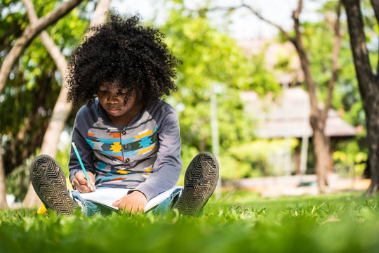A little boy writing on notebook while sitting on green grass in a park